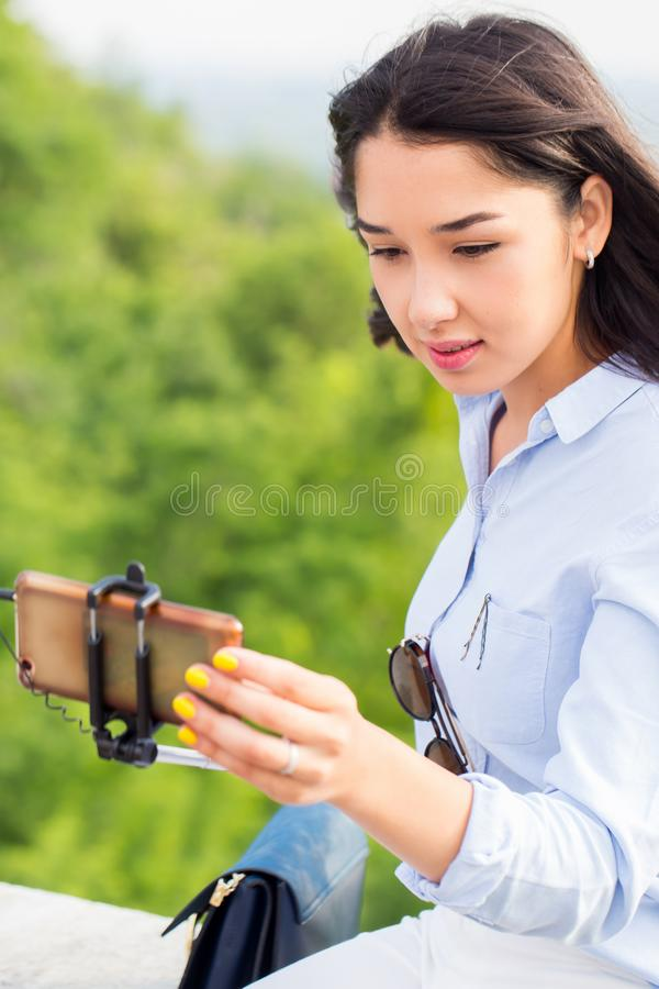 Close-up portrait of a beautiful brunette woman taking a selfie. Modern technology, selfie stick. Close up portrait of a beautiful brunette woman taking a royalty free stock images