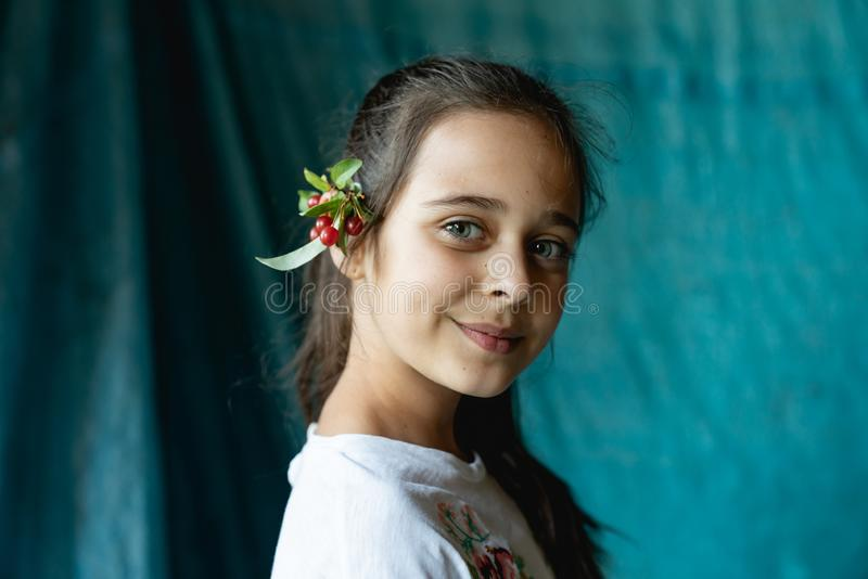 Close up portrait of beautiful brunette young girl with a branch of viburnum behind her ear that looking at the camera stock image
