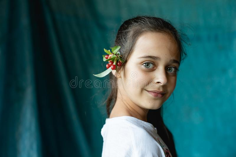 Close up portrait of beautiful brunette young girl with a branch of viburnum behind her ear that looking at the camera royalty free stock photos