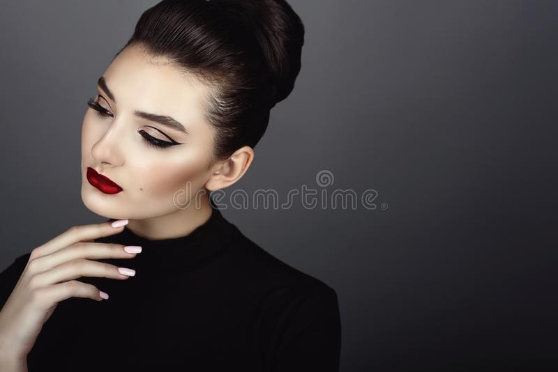 Beautiful dark haired model with perfect artistic make up and hair scraped back into a high bun stock photos