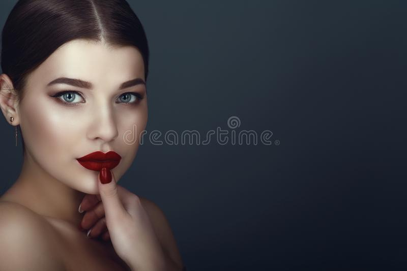 Close up portrait of beautiful dark-haired model with perfect make up and centre part sleek bun touching her ideal shaped lips royalty free stock image