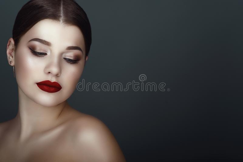Close up portrait of beautiful dark-haired model with perfect make up and centre part sleek ponytail looking down stock photography