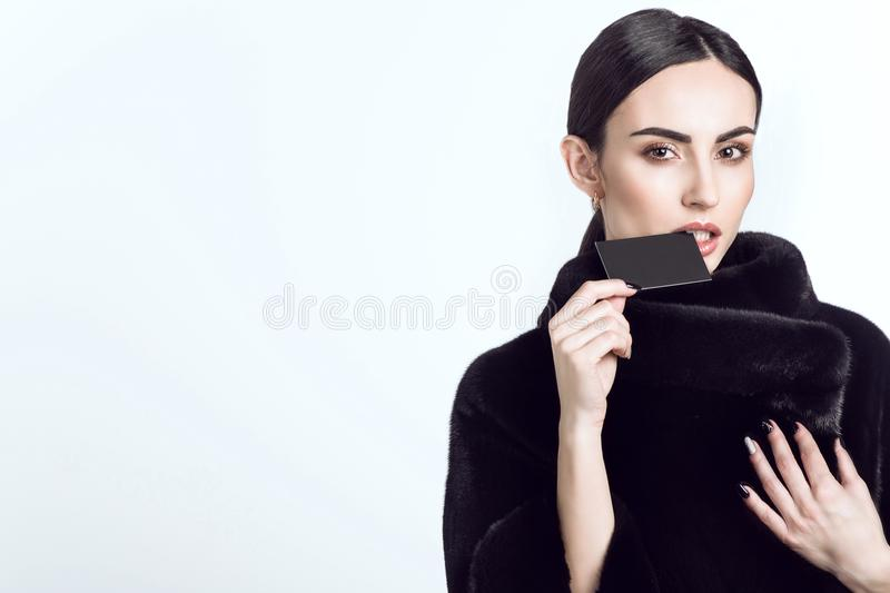Beautiful model wearing dark mink fur coat and biting the edge of a black blankbusiness card royalty free stock photos