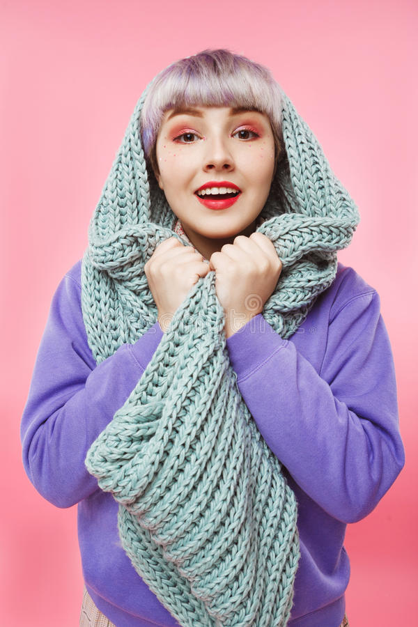 Close-up portrait of beautiful dollish girl with short light violet hair wearing lilac sweater and grey knitted. Neckwarmer over pink background. Copy space royalty free stock photo