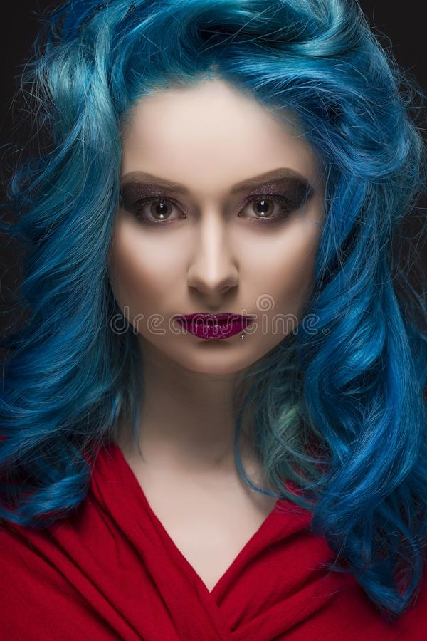 Close-up portrait of beautiful dyed blue colour hair girl wearing red scarf. Hairdressing salon, coloring hair, advertising and commercial design royalty free stock photo