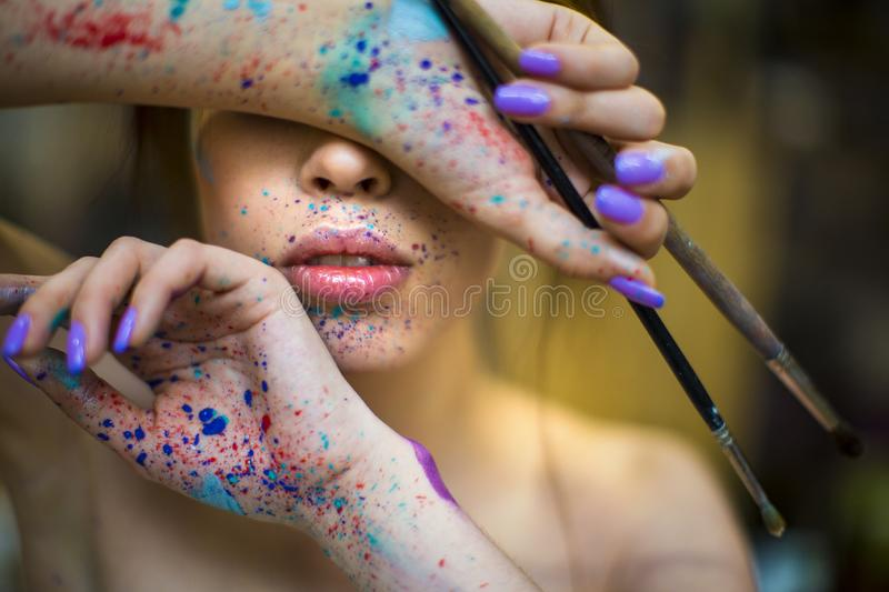 Close up portrait of beautiful female artist with dirty hands with different paints on them, holding paint brushes near royalty free stock image