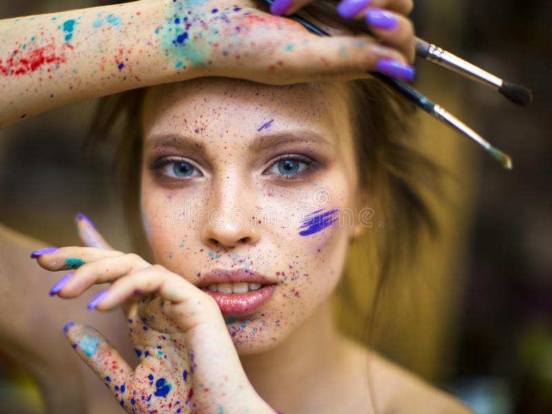 Close up portrait of beautiful female artist with dirty hands with different paints on them, holding paint brushes near stock photos