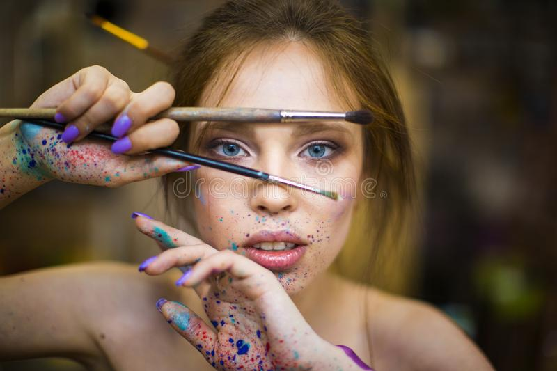 Close up portrait of beautiful female artist with dirty hands with different paints on them, holding paint brushes near royalty free stock images