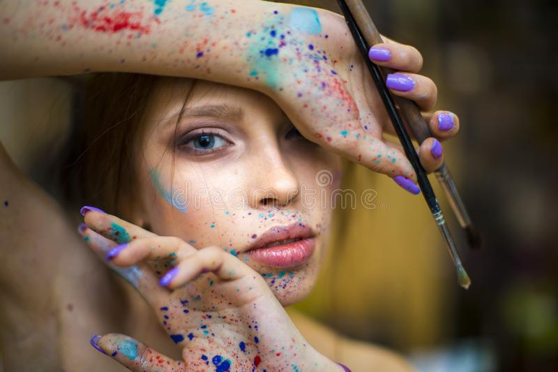 Close up portrait of beautiful female artist with dirty hands with different paints on them, holding paint brushes near stock photo