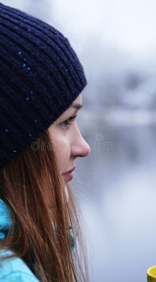 Close up portrait of a beautiful girl dreaming looking into the distance standing outdoor with cup of tea. royalty free stock photo