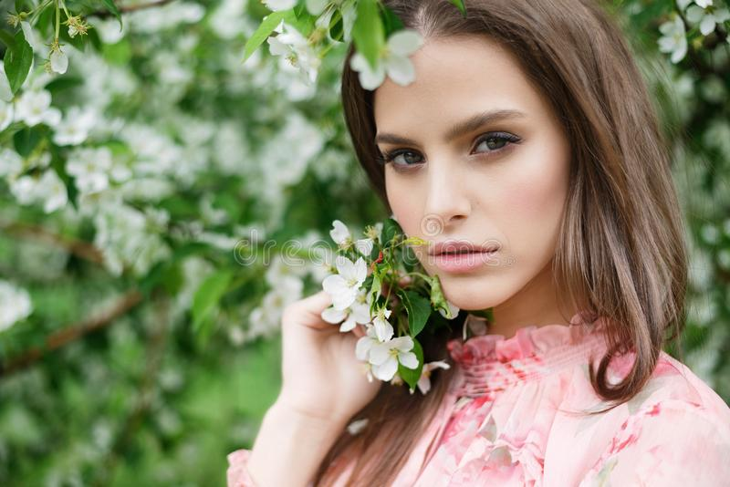 Close-up portrait of a beautiful girl in flowering trees. Flowering fruit trees stock images