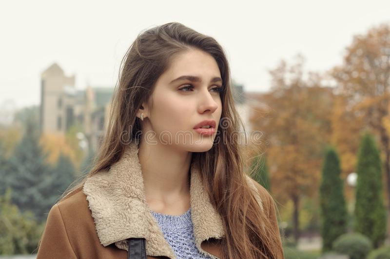 Close-up portrait of a beautiful girl with long brown hair. And clean smooth skin who walks outdoors stock photo