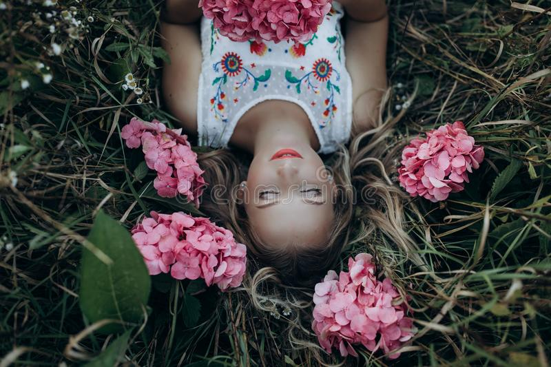 Close up portrait of a beautiful girl lying in a field with flowers royalty free stock photos