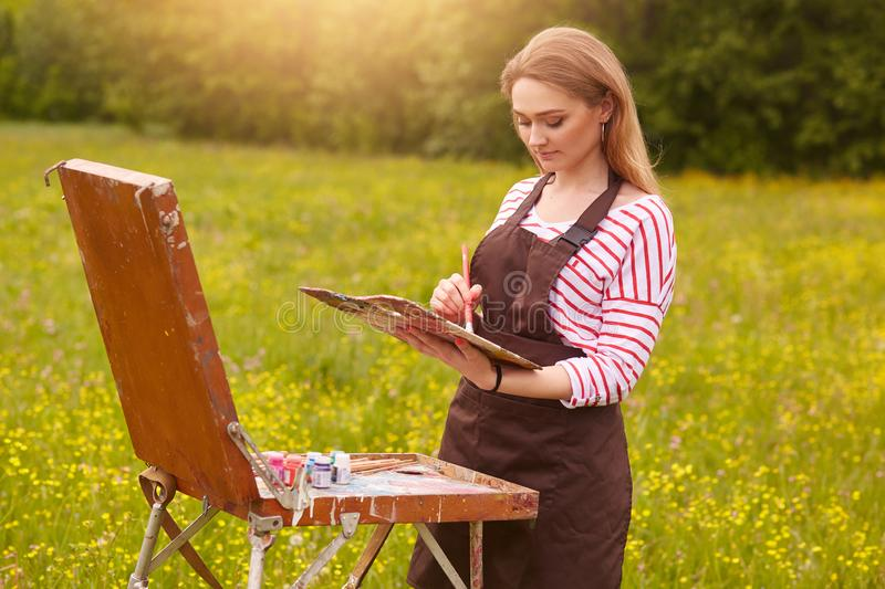 Close up portrait of beautiful girl with painting picture on easel in nature, young attractive woman involved in creativity and stock photos