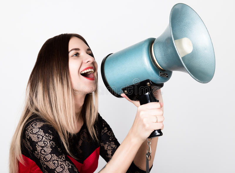 Close-up portrait of a beautiful girl in a red dress with lace sleeves, she yells into a bullhorn. Public Relations.  royalty free stock photos