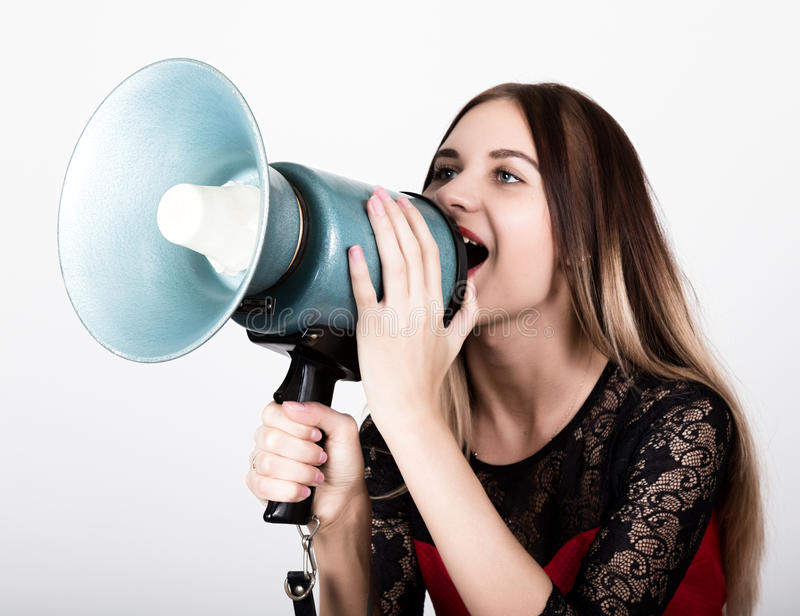 Close-up portrait of a beautiful girl in a red dress with lace sleeves, she yells into a bullhorn. Public Relations.  stock photos