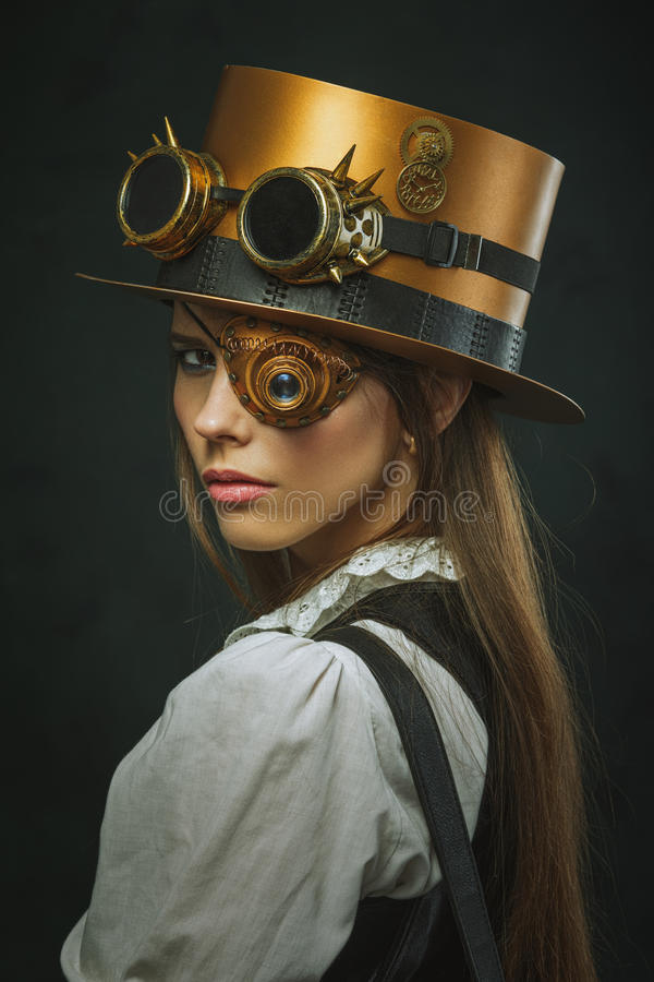 Close-up portrait of a beautiful girl steampunk, hat and eyecup. stock image