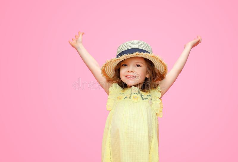Close up portrait of a Beautiful girl in yellow dress and straw hat. Pretty tenderness kid holding hands up in great happiness and looking at camera, posing on stock photos