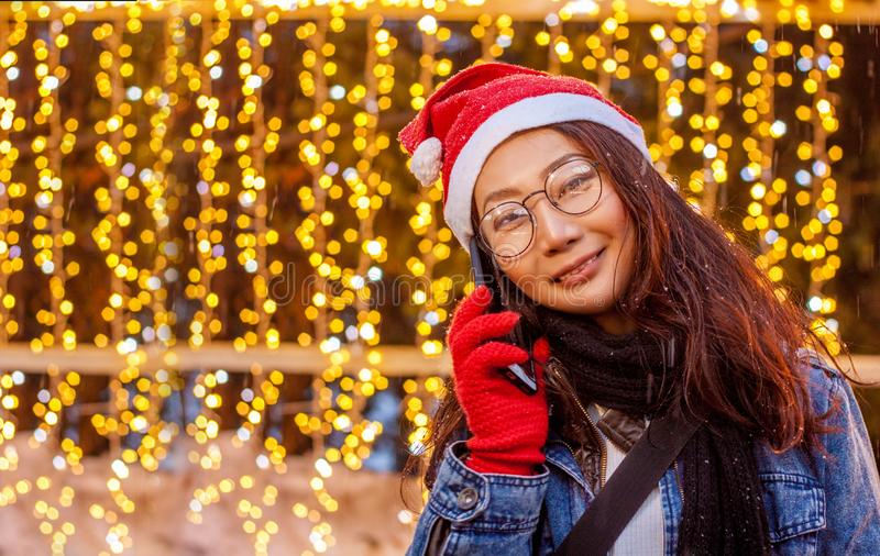 Close-up portrait of a beautiful happy Asian girl in a red Santa Claus hat holding a smartphone stands near the lights and Christm stock photos