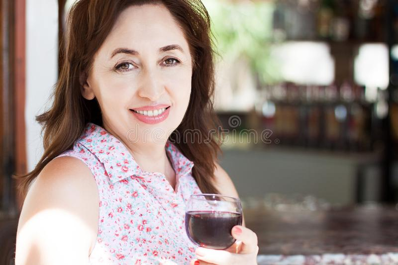 Close-up portrait of beautiful happy middle aged woman holds a glass of wine at the resort on her vacation, summer concept royalty free stock photo