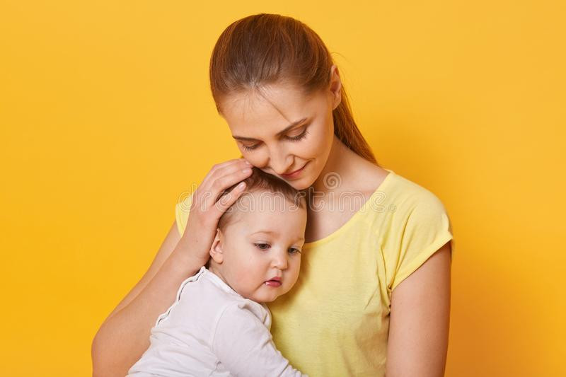 Close up portrait of beautiful happy mother hugging her baby girl with love, mom wears casual t shit with ponytail, pose in photo stock photography