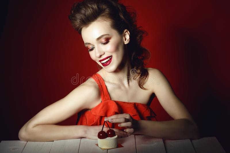 Beautiful happy young woman with creative hairstyle and colourful make up sitting at the wooden table and looking at pastry stock photo