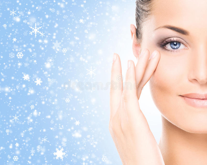 Close-up portrait of a beautiful and healthy woman on the snow. Spa portrait of young and beautiful woman over winter Christmas background royalty free stock images