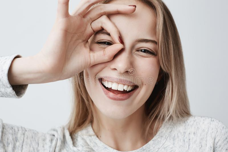 Close up portrait of beautiful joyful blonde Caucasian female smiling, demonstrating white teeth, looking at the camera royalty free stock photos