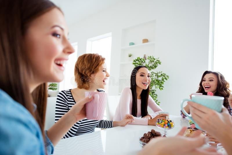 Close up portrait beautiful she her ladies buddies meeting sit round big white table bright kitchen hold cups listen stock photography