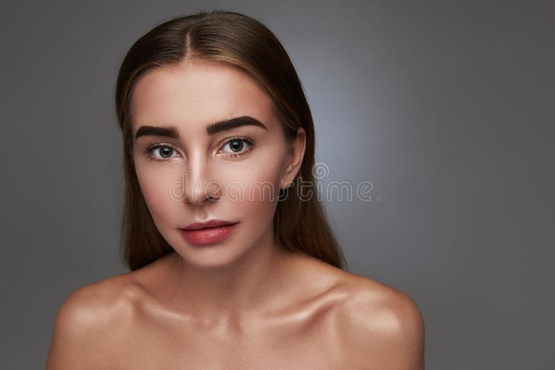 Attractive young woman posing against gray background stock photography