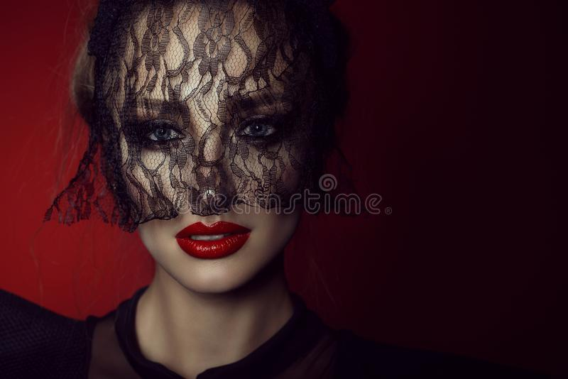 Close up portrait of a beautiful lady with vivid blue eyes and perfect make up hiding her face behind the lace black veil royalty free stock photo