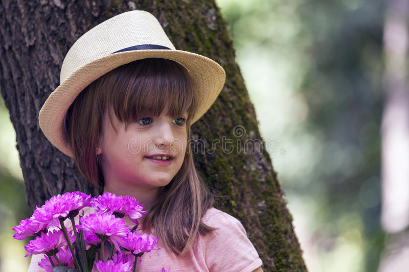 Close up portrait of a beautiful little girl with big blue eyes, with a hat while holding a bouquet of flowers royalty free stock image