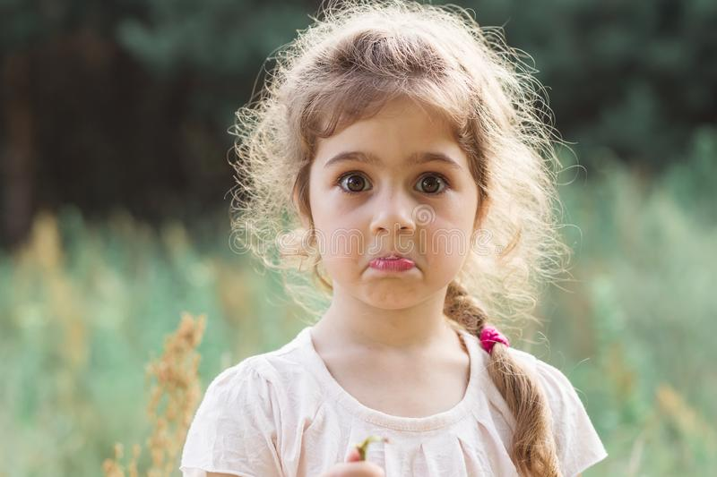 Close up Portrait of beautiful little Girl holding her head in amazement and surprised with something at summer day stock images