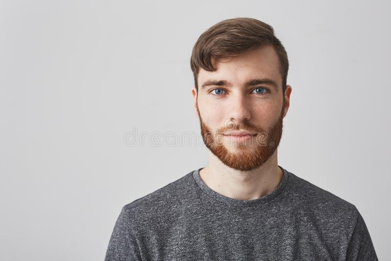 Close up portrait of beautiful manly bearded guy with stylish hairstyle smiling, looking in camera with happy and calm. Face expression stock image