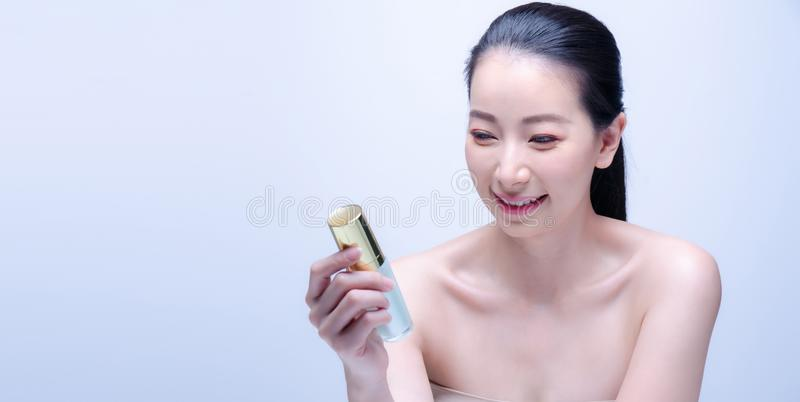 Close-up portrait of beautiful mature asian woman is holding beauty bottle of serum for applying makeup foundation . Skin care and. Close-up portrait of mature stock photography
