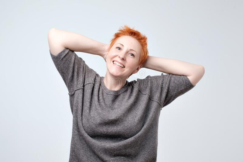 Close up portrait of beautiful mature woman with red hair smiling and standing by wall stock images