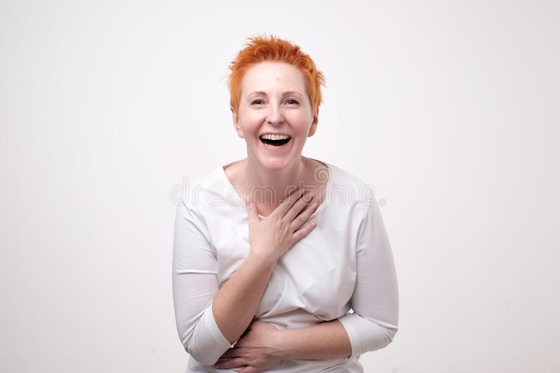 Close up portrait of a beautiful mid adult woman with red hair laughing standing on gray background. royalty free stock photos