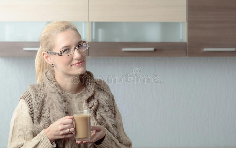 Close-up portrait of a beautiful mid age woman in glasses with cup of coffee. Attractive and happy blonde in sweater drinks latte. Copy space stock photos