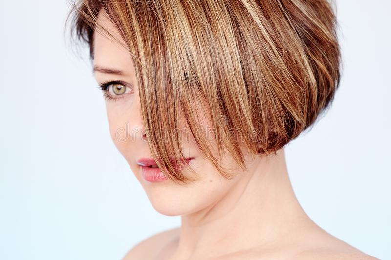 Woman with short haircut. Close up portrait of beautiful middle aged woman with elegant short haircut and natural fresh makeup over blue background - mature stock photos
