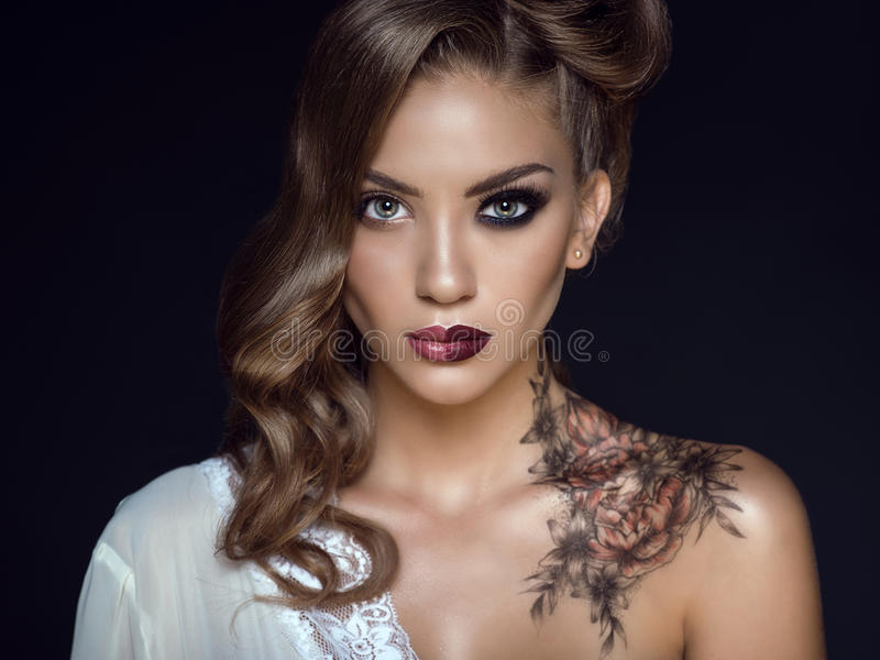 Close up portrait of beautiful model with artistic make up and hairstyle. Floral body art on her shoulder. Ideal woman concept. One half symbolizes a good stock photo