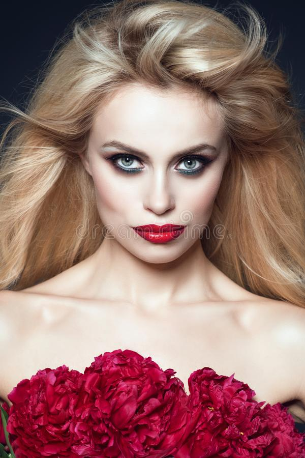 Close up portrait of beautiful model with blond hair blowing in the wind and perfect make up. Bunch of peonies covering her breast stock photo