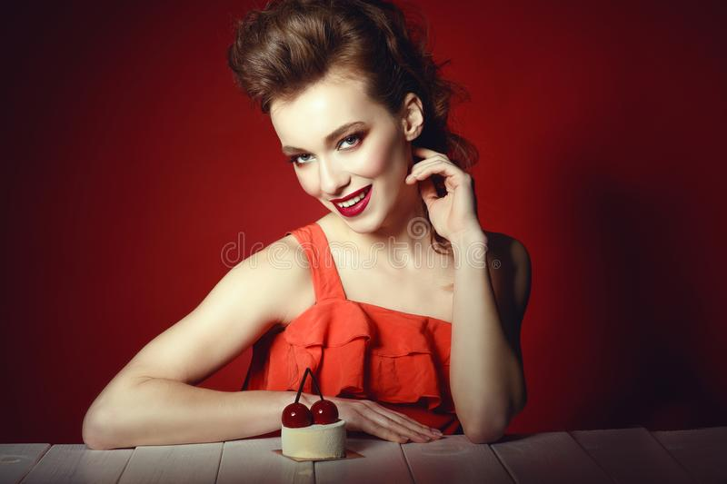 Beautiful model with creative hairstyle and colourful make up sitting at the wooden table with delicious cherry pastry on it stock photos