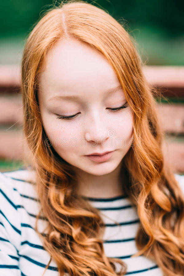 Close-up portrait of beautiful modest girl with long curly red hair in summer park. Outdoor portrait of a red-haired teenage girl stock images