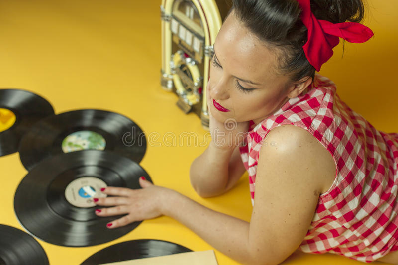 Close up portrait beautiful pin up girl with old vinil records. Isolated yellow background royalty free stock photos