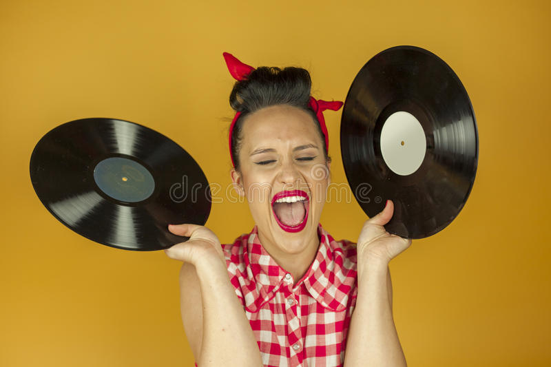 Close up portrait beautiful pin up girl with old vinil records. Isolated yellow background stock images