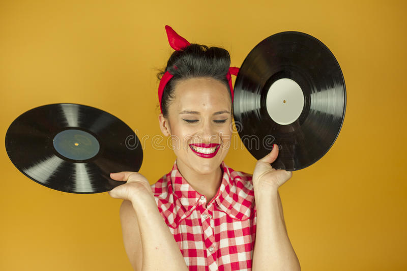 Close up portrait beautiful pin up girl with old vinil records. Isolated yellow background stock image