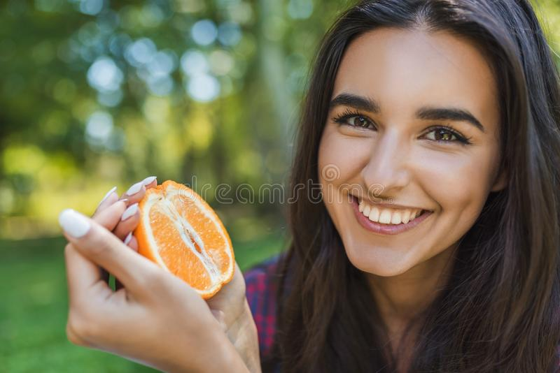 Close up portrait of beautiful pretty brunette smiling woman holding juicy delicious orange at green park background. Young female stock photography