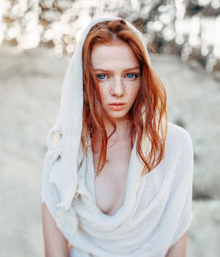 Close up portrait of a beautiful red haired girl in white medieval dress on glowing sun. Fairy tale story about brave heart woman royalty free stock photography