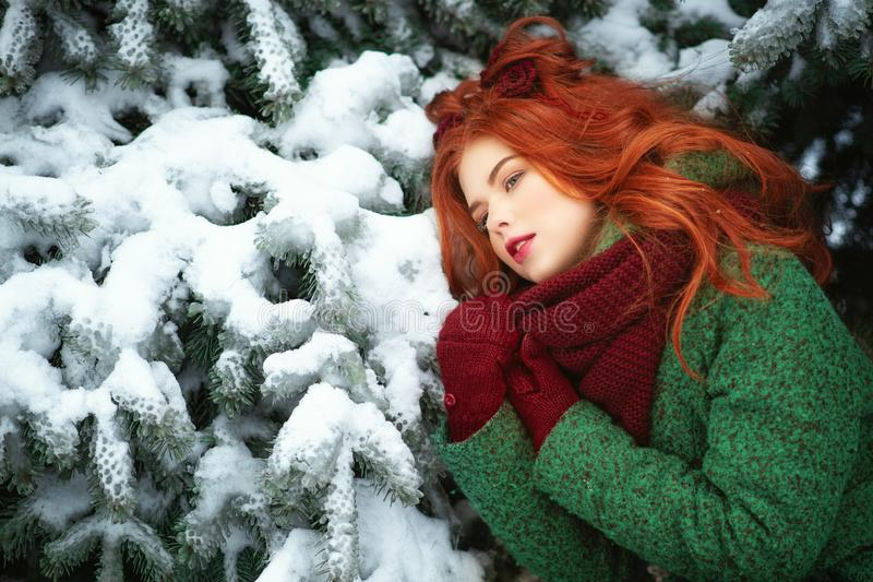 Close up portrait of a beautiful red-haired girl leaning on snowy fir tree bough with dreaming look. royalty free stock photos
