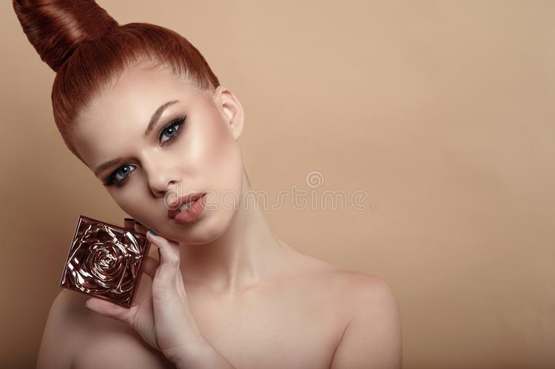 Close up portrait of beautiful red-haired woman with perfect make-up and hair scraped back into a high bun holding compact powder royalty free stock images